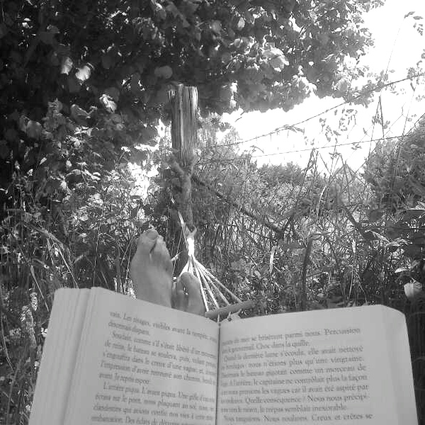 Lying in the hammock reading a book
